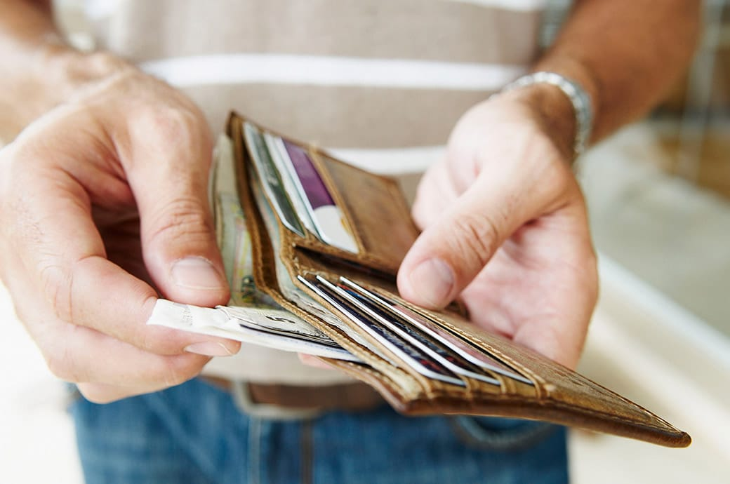 A close up of someone taking out bills from a wallet